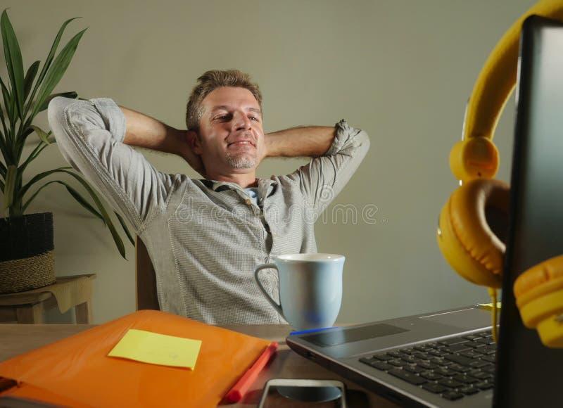 倾斜在椅子的年轻满意和确信的商人放松了在家工作有便携式计算机的办公室坐书桌sm 库存照片