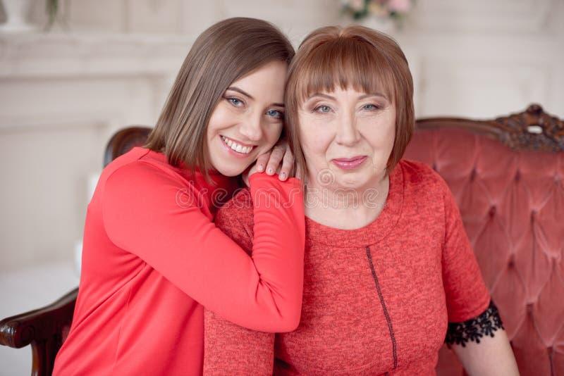 倾斜在母亲肩膀的美丽的微笑的妇女 免版税库存图片
