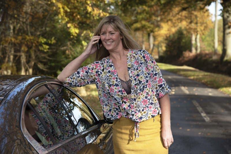 倾斜在汽车的妇女司机使用一个手机 库存图片