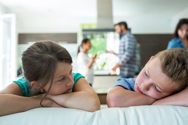 倾斜在沙发的哀伤的孩子,当父母争论在背景中时 库存图片