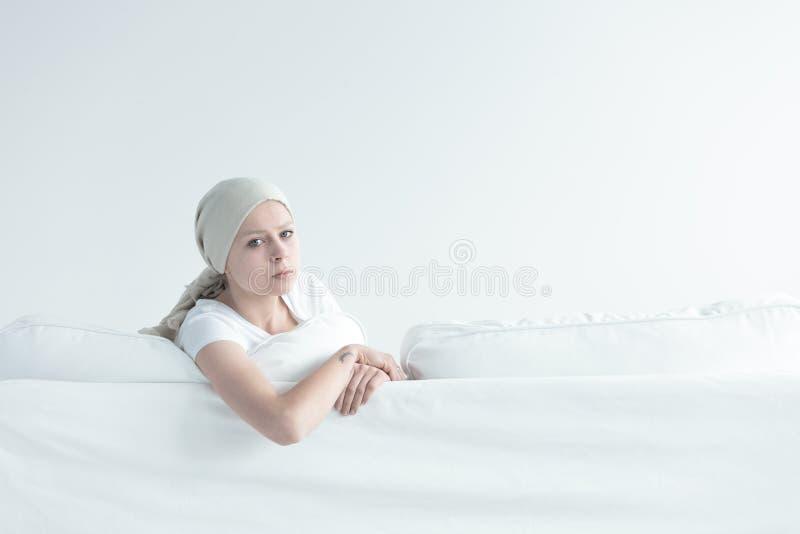 倾斜在沙发的病的女孩 免版税图库摄影