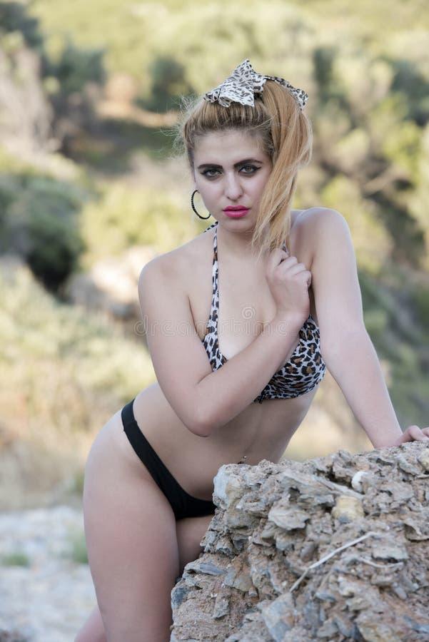 倾斜在海岩石的女服比基尼泳装 免版税库存图片