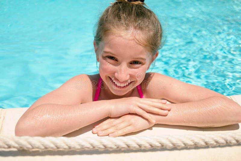倾斜在游泳池边缘的十几岁的女孩  免版税图库摄影