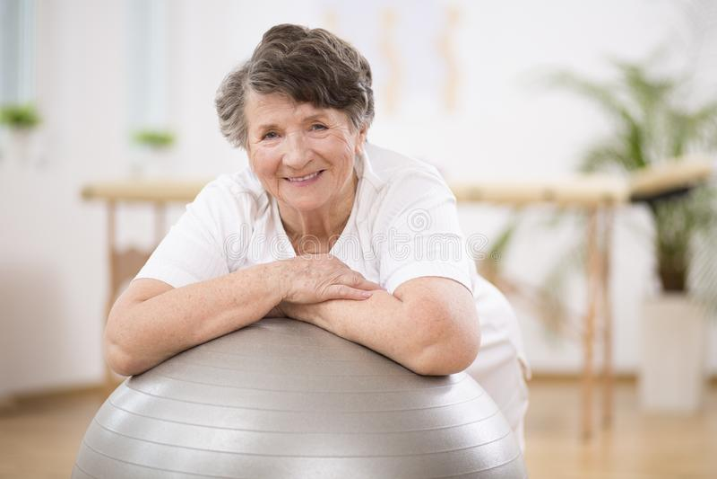 倾斜在灰色体操球的资深妇女在物理疗法中心 免版税库存图片