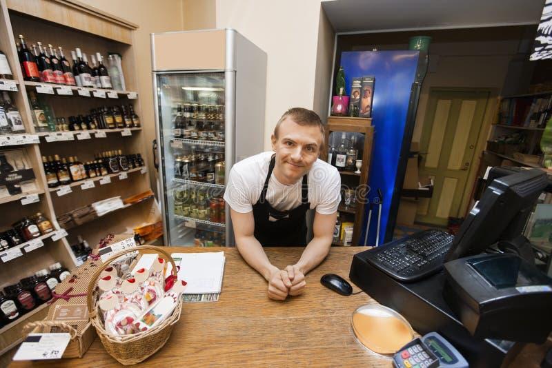 倾斜在现金柜台的推销员画象在超级市场 免版税库存图片