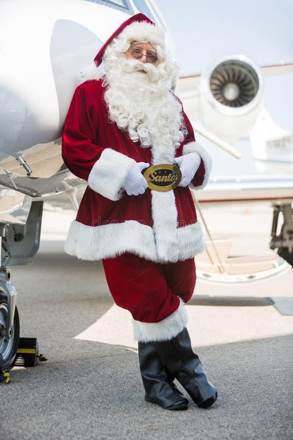 倾斜在私人喷气式飞机的圣诞老人在机场终端 免版税库存照片