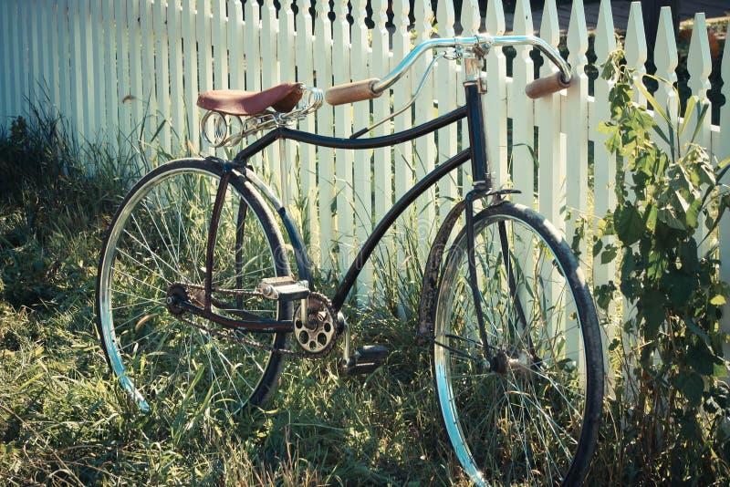 倾斜在篱芭的古色古香的自行车 库存照片