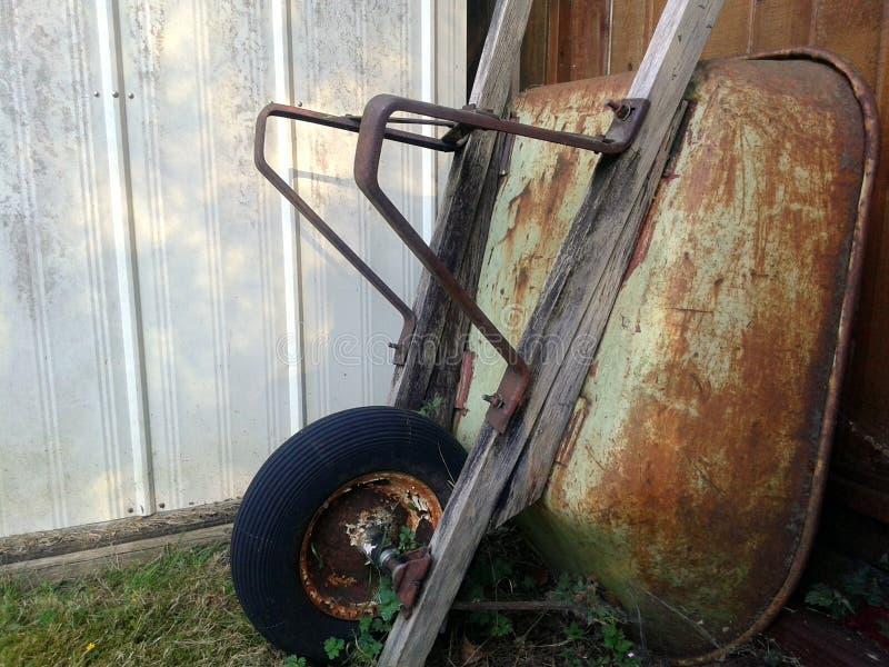 倾斜在篱芭的生锈的独轮车 库存图片