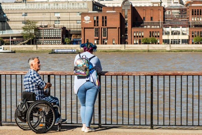 倾斜在篱芭的轮椅和妇女的人在Conversati 免版税库存图片