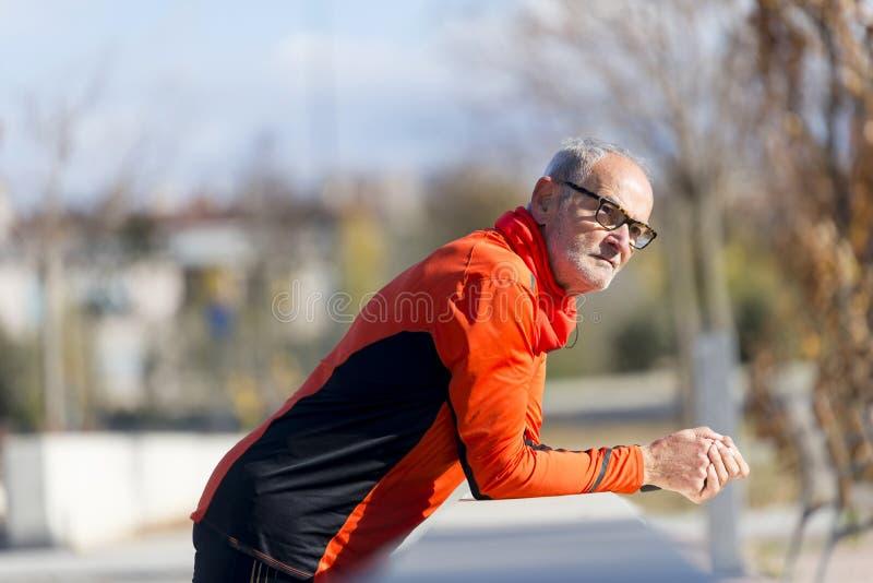倾斜在篱芭的运动老人画象  图库摄影