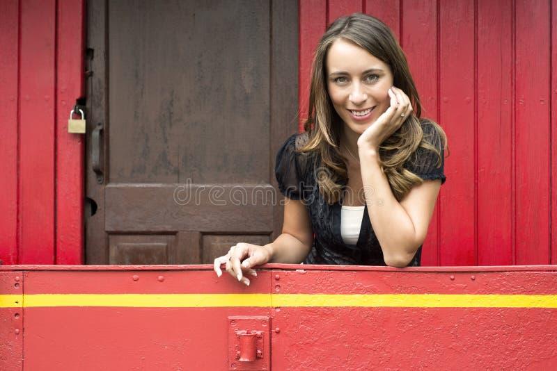 倾斜在红色守车汽车的栏杆的妇女 库存照片