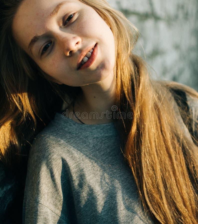 倾斜在织地不很细石墙的美丽的少年女孩画象户外,看起来微笑对照相机 免版税库存照片