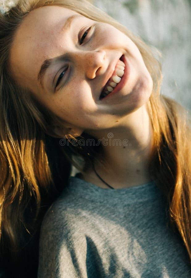 倾斜在织地不很细石墙的美丽的少年女孩画象户外,看起来微笑对照相机 库存图片
