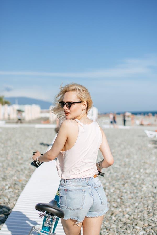 倾斜在自行车的妇女,当站立海滩的时近的观察台 库存图片