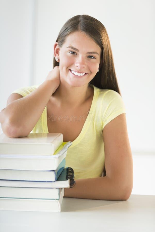 倾斜在被堆积的书的少年学生在书桌 图库摄影