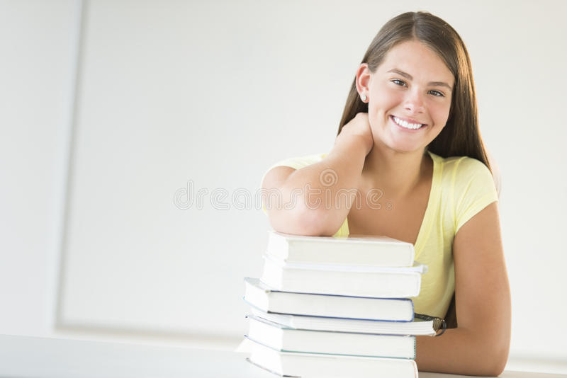 倾斜在被堆积的书的少年学生在教室 免版税库存图片