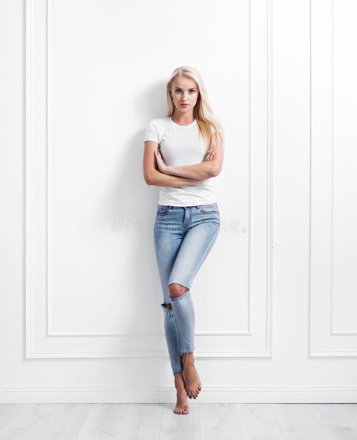 倾斜在装饰墙壁的年轻白肤金发的妇女 免版税库存照片