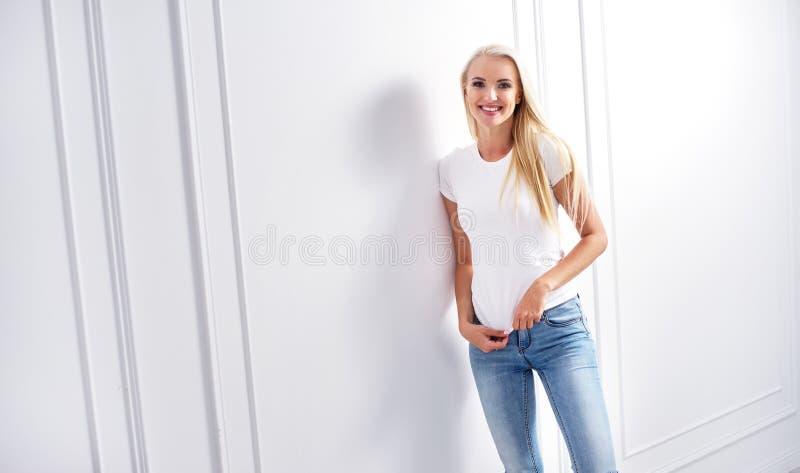 倾斜在装饰墙壁的年轻白肤金发的妇女 库存照片