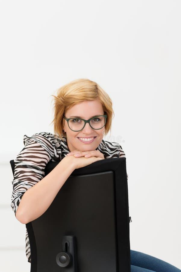 倾斜在计算机显示器的年轻女实业家 免版税图库摄影