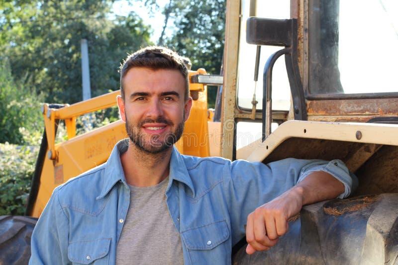倾斜在谷仓的英俊的农夫在拖拉机轮子 免版税库存图片