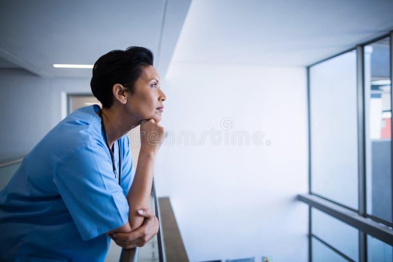倾斜在走廊的栏杆的体贴的女性护士 库存照片