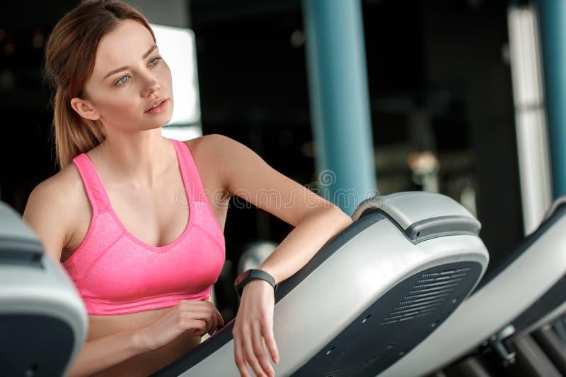 倾斜在踏车的健身房健康生活方式的少女看周道的窗口 图库摄影