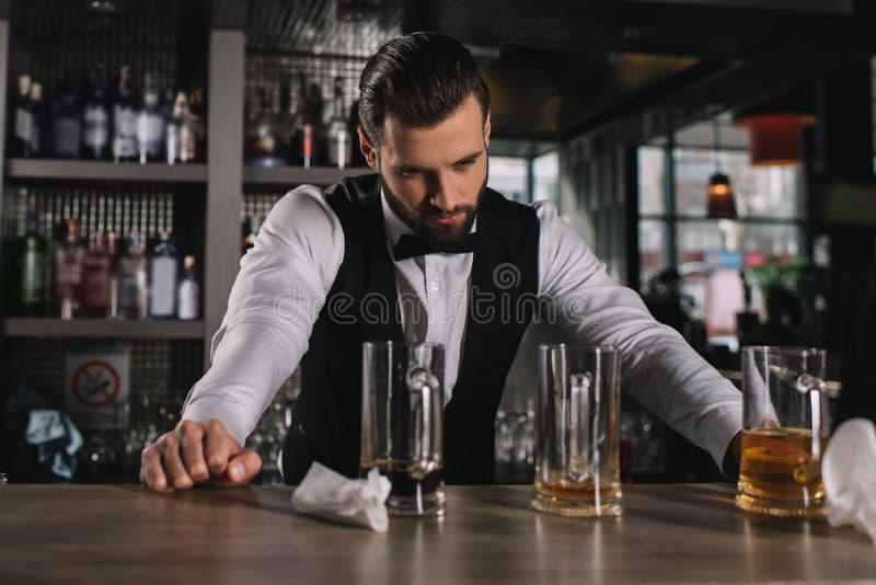 倾斜在酒吧柜台和看肮脏的玻璃的疲乏的英俊的侍酒者 免版税库存照片