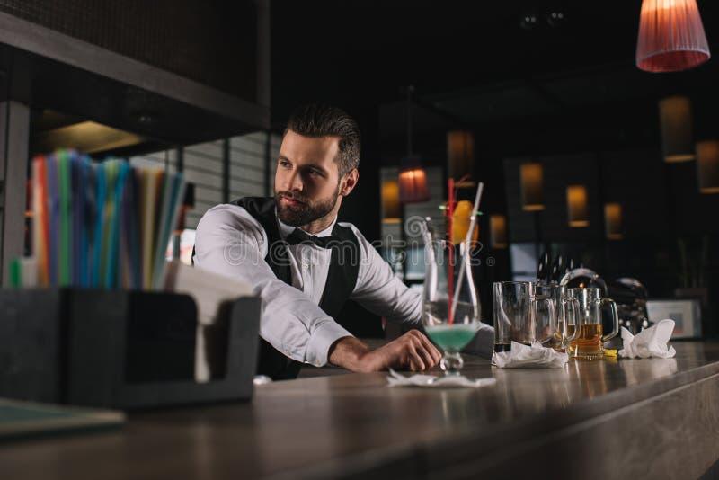 倾斜在酒吧柜台的英俊的侍酒者 图库摄影