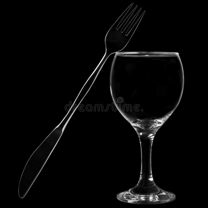 倾斜在酒杯的刀子和叉子 免版税库存图片