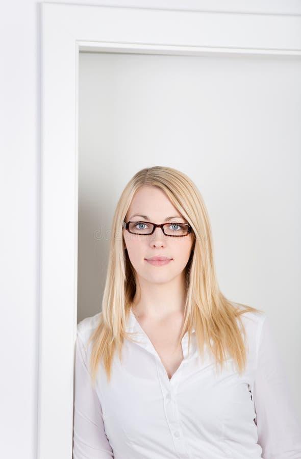 倾斜在门的年轻白肤金发的女实业家 库存图片