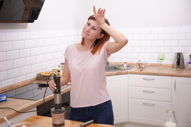 倾斜在食品加工器的疲乏的主妇,当在家时烹调在厨房 复杂的食谱 库存图片