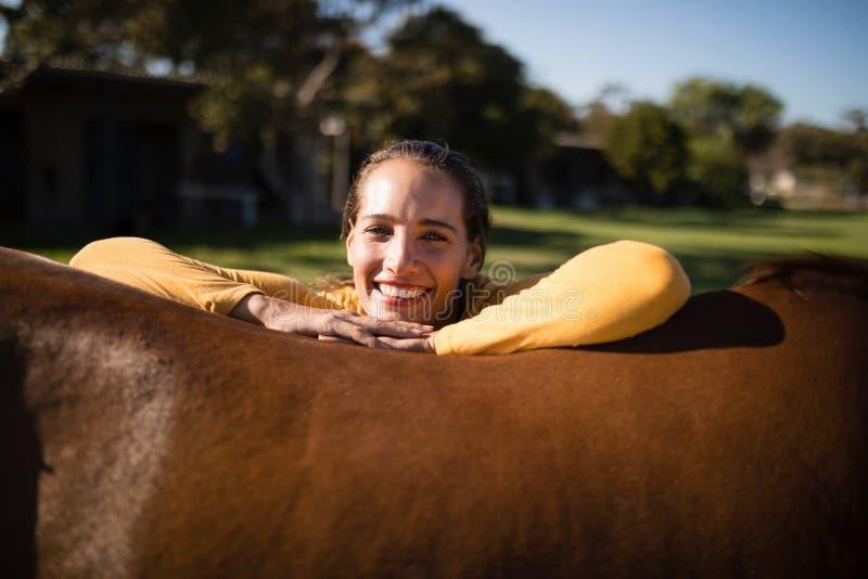 倾斜在马的愉快的女性骑师在谷仓 免版税库存照片