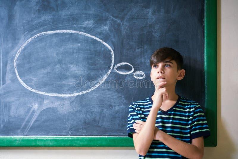 倾斜在黑板和认为在学校的男孩学生 库存图片