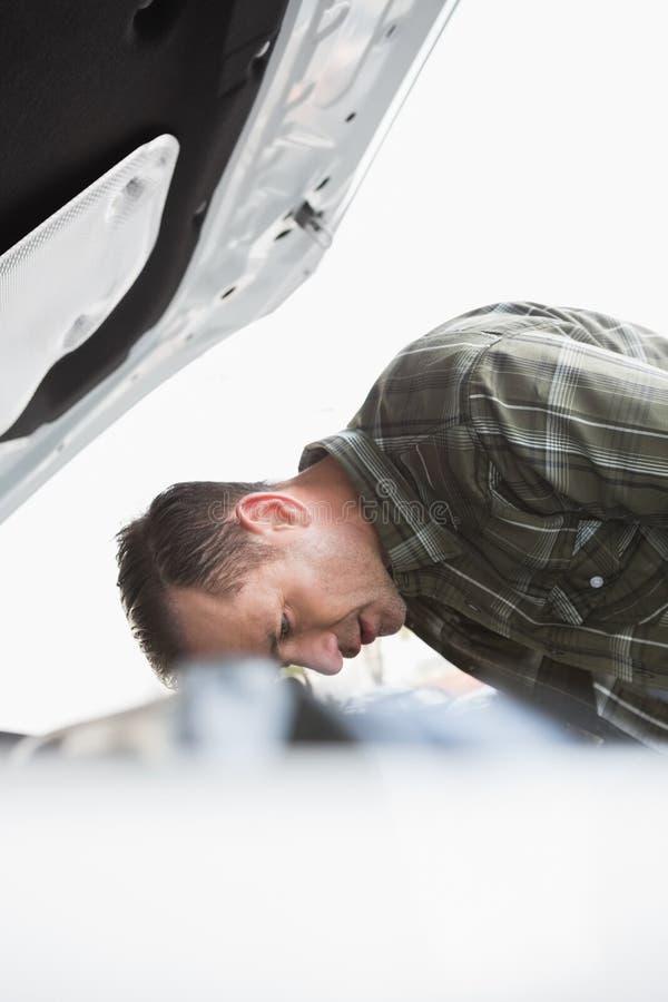 倾斜在他的汽车的生气商人 免版税库存图片