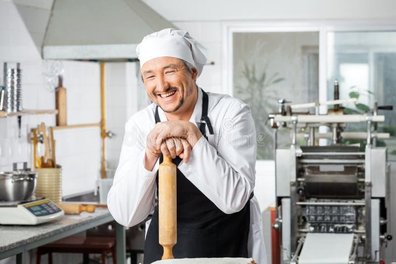 倾斜在滚针的快乐的厨师 免版税库存图片