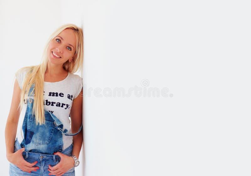 倾斜墙壁的美丽的白肤金发的妇女画象  免版税图库摄影
