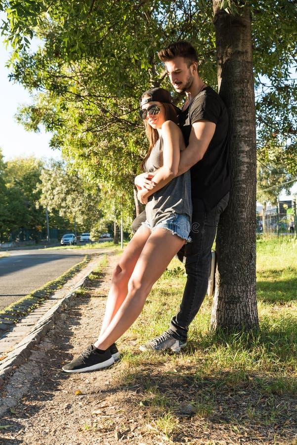 倾斜对一棵树的年轻夫妇在一个城市环境里 免版税库存照片