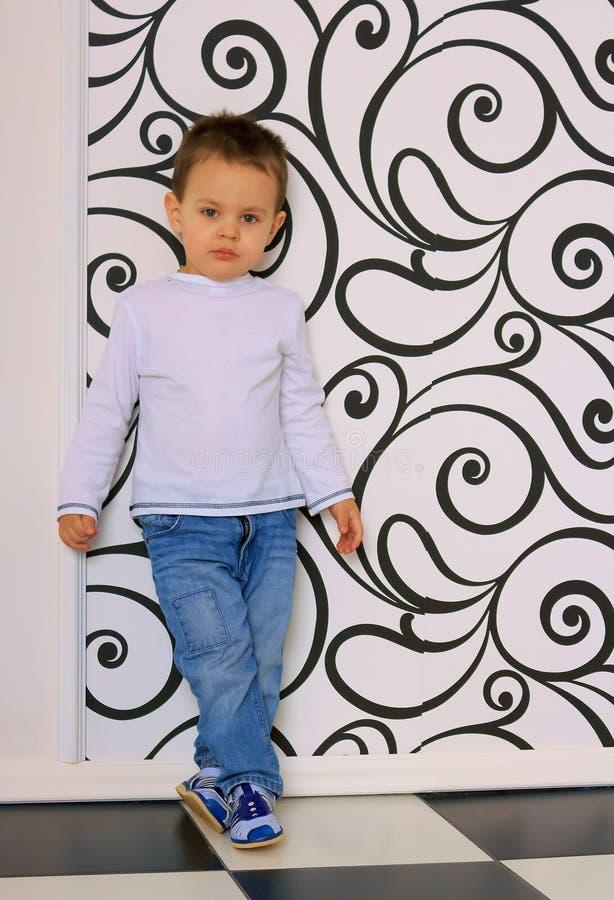 倾斜对墙壁的体贴的男孩 库存照片