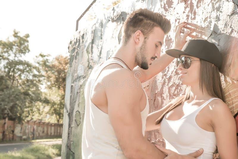 倾斜对墙壁的年轻夫妇在一个城市环境里 免版税图库摄影