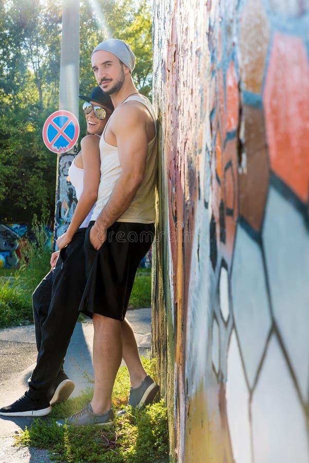 倾斜对墙壁的年轻夫妇在一个城市环境里 图库摄影