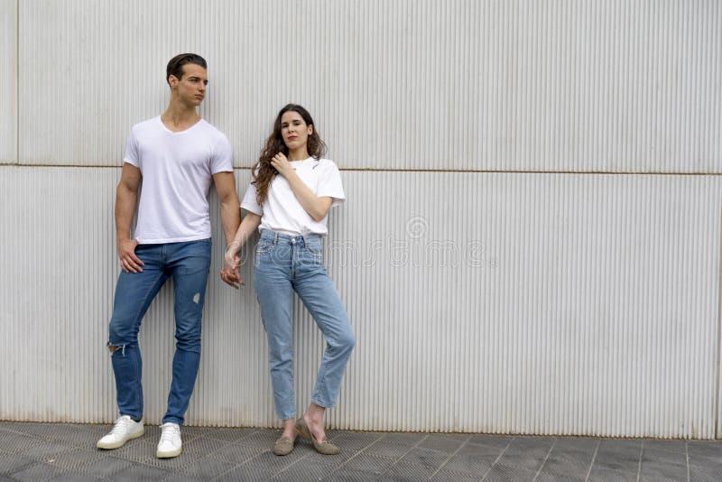 倾斜对墙壁的愉快的夫妇握穿便服的手在一明亮的天 库存图片