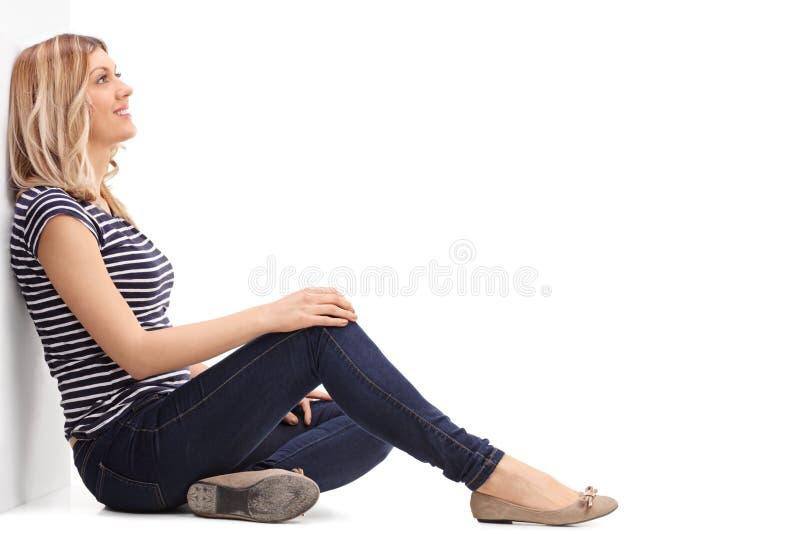 倾斜对墙壁的沉思白肤金发的妇女 库存照片
