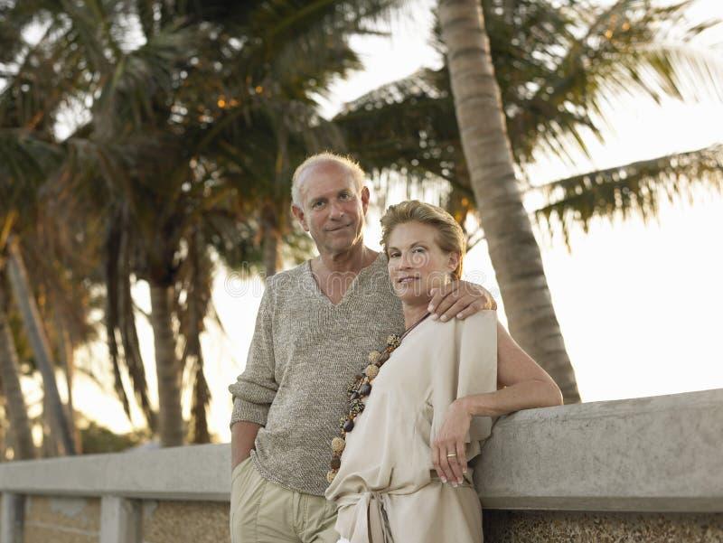 倾斜对墙壁的爱恋的资深夫妇在海滩 免版税库存照片