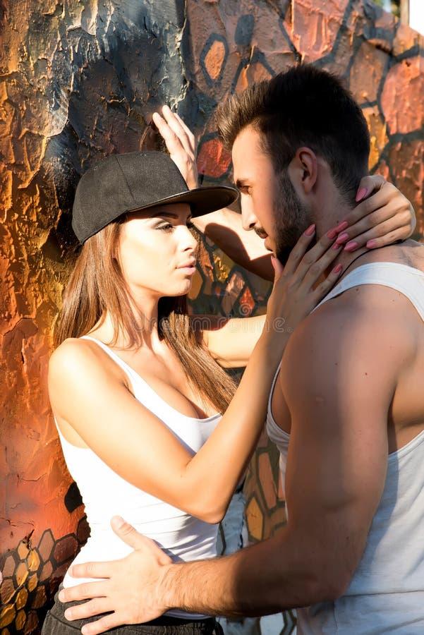 倾斜对墙壁的年轻夫妇在一个城市环境里 库存图片