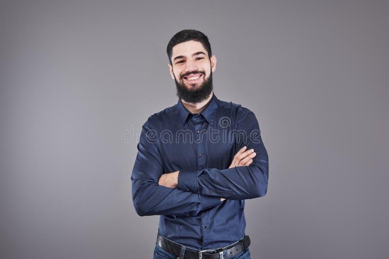 倾斜对有横渡的胳膊的灰色墙壁的年轻英俊的人 有胡子的一个严肃的年轻人看照相机 免版税库存图片