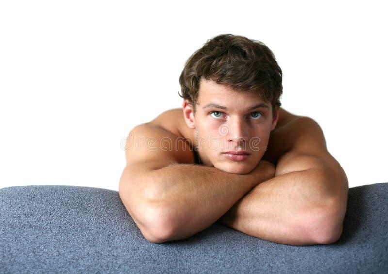 倾斜的人肌肉性感的沙发 免版税库存图片