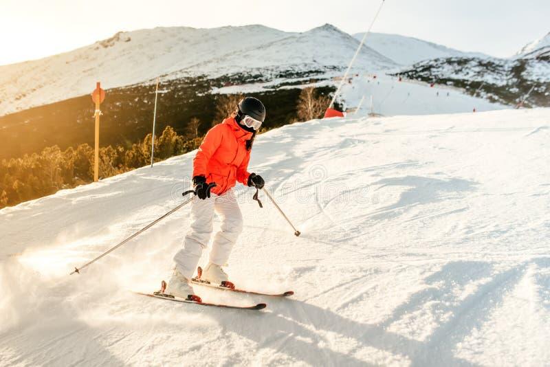 倾斜的女子滑雪者在山 女孩滑雪在一个晴天 图库摄影