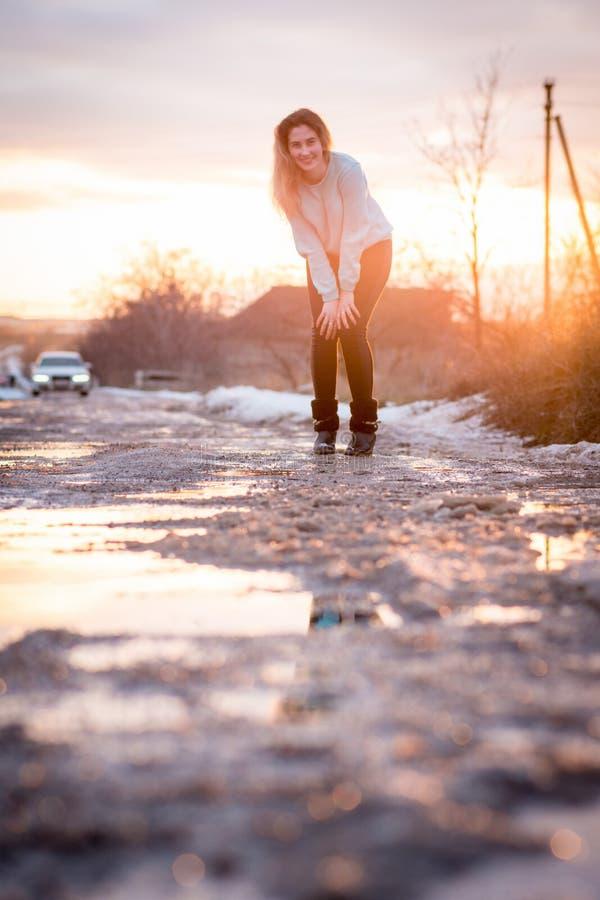 倾斜的女孩在用水坑盖的路站立 晚上照片充斥与阳光 免版税库存图片