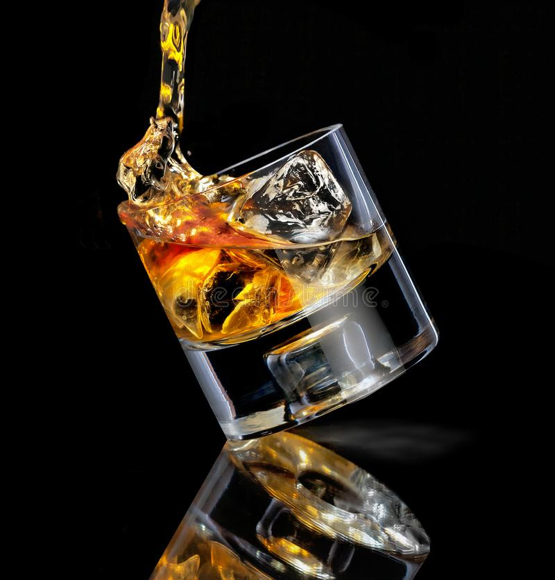 倾斜的时尚威士忌酒杯 在带反射的黑色背景上浇过立方冰 图库摄影