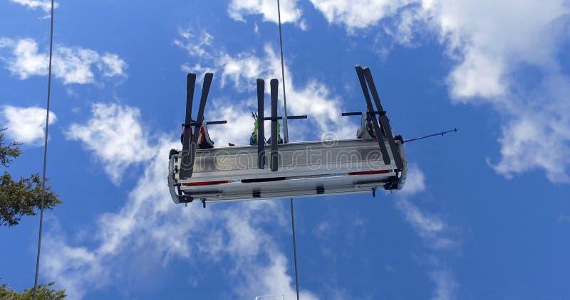 倾斜的滑雪电缆车运载的滑雪者在山顶部 免版税库存照片